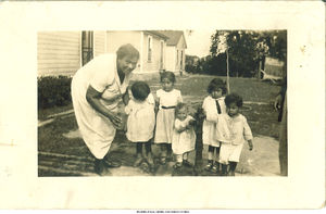 Muggie Adams Rodriguez with children gathered around pump, Bettendorf, Iowa, 1924