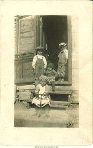 Estefania Joyce Rodriguez on tricycle, brothers Albert on left, standing, Tom standing, and John sitting on step, Bettendorf, Iowa, ca. 1925
