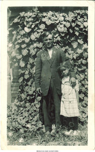 Charles Rivera with his daughter Nestora Rivera in front of vines, Buxton, Iowa, ca. 1920