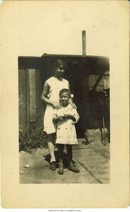 Nestora Rivera Rodriguez standing with her sister Estefania Joyce Rodriguez in front of boxcars in Holy City, Bettendorf, Iowa, 1929