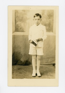 Henry Vargas, a Mexican American boy dressed for First Holy Communion, holding a book in his hand.